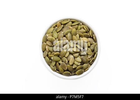 Pumpkin seeds in a cup from above isolated on a white background. - Stock Photo