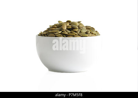 A cup of pumpkin seeds isolated on a white background. - Stock Photo