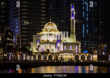 Beautiful illuminated mosque in Dubai marina at night, long exposure, Dubai, United Arab Emirates - Stock Photo
