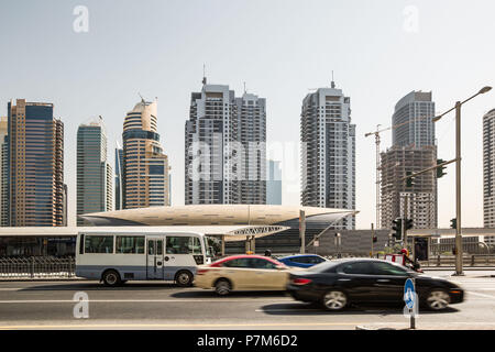 Cars on the street in front of futuristic building of Dubai metro station and modern skyscrapers in Dubai, United Arab Emirates - Stock Photo