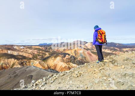 A trekker is looking at the Landmannalaugar panorama from the top of Blahnukur mountain, Landmannalaugar, Fjallabak Nature Reserve, Highlands, Southern Region, Iceland, Europe, - Stock Photo