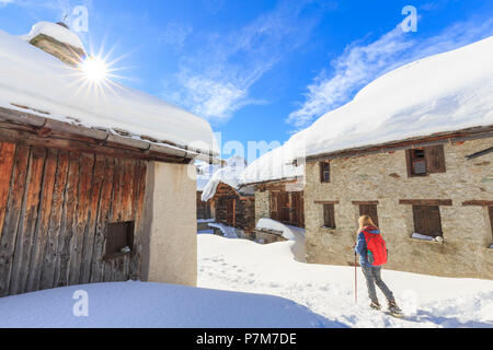 Young girl walk with snowshoes in the village of Grevasalvas, Engadin Valley, Graubünden, Switzerland, Europe. - Stock Photo