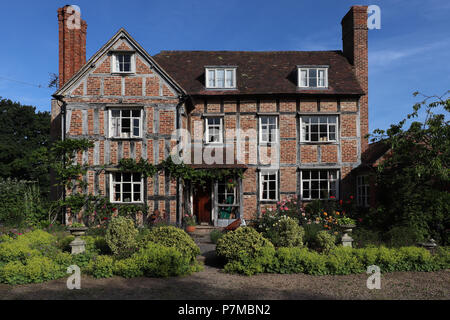 Lovely three story 17th C. country house in England constructed with brick infill on a timber frame, the timbers exposed, large chimneys, & wisteria - Stock Photo