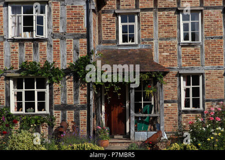 Close up view of a post and beam constructed 17th Century house in  England; exposed timbers, brick infill on framework, wisteria over [front porch. - Stock Photo