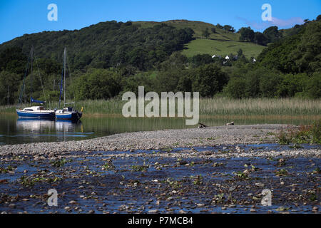 Two sail boats moored near a reedy marsh, with hills and farmland in the distance, on Coniston Water, in the Lake District, UK, gravel bar from beck. - Stock Photo