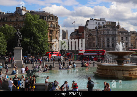 View of Trafalgar Square, City of Westminster (London) looking down Whitehall towards the Victoria Tower of Parliament; double decker busses, tourists - Stock Photo