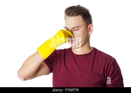 Young man wearing yellow gloves and holding cleaning supplies, housekeeper - Stock Photo