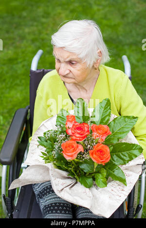 Disabled elderly woman sitting in wheelchair, receiving a flower bouquet for her birthday - Stock Photo
