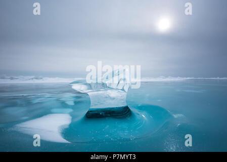 Piece of ice with sun reflection at lake Baikal, Irkutsk region, Siberia, Russia - Stock Photo