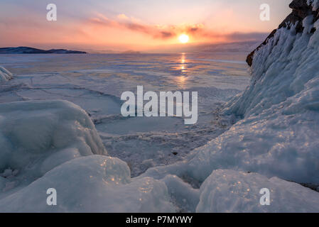 Ice stalactites in a cave at the shore at sunset at lake Baikal, Irkutsk region, Siberia, Russia - Stock Photo