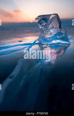 A cube of ice on the flat frosen lake at sunset, Baikal, Irkutsk region, Siberia, Russia - Stock Photo