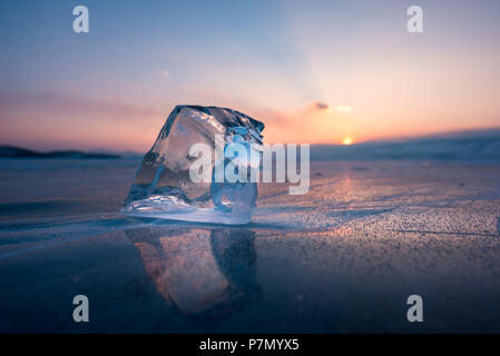 A cube of ice on the flat frosen lake at sunset, Baikal, Irkutsk region, Siberia, Russia - Stock Photo