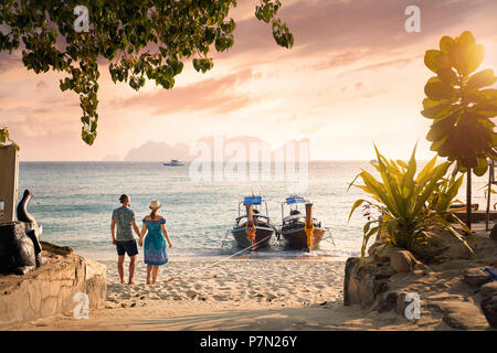 Happy couple on the tropical beach of Phi Phi island at sunset in Southern Thailand. Travel magazine concept. - Stock Photo
