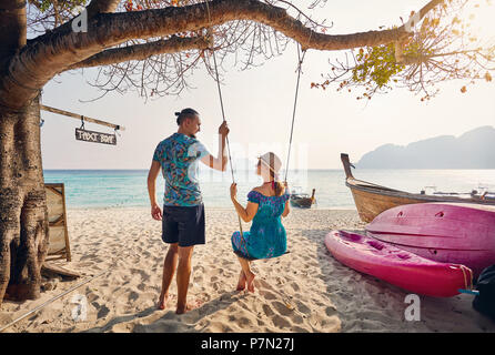 Happy couple on the tropical beach of Phi Phi island in Southern Thailand. Travel magazine concept. - Stock Photo