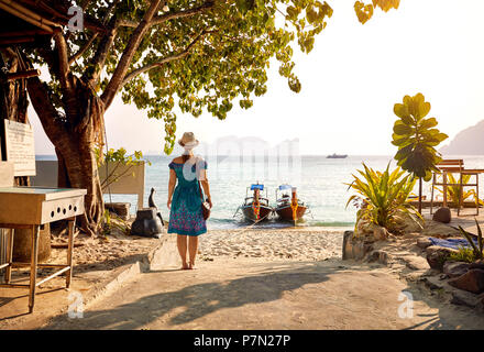 Beautiful woman in green drees on the tropical beach of Phi Phi island at sunset in Southern Thailand. Travel magazine concept. - Stock Photo