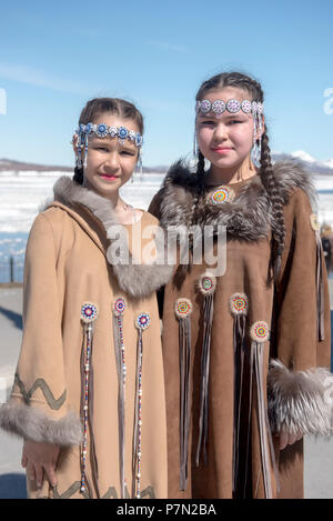Two Chukchi girls in folk dresses against spring Arctic landscape - Stock Photo