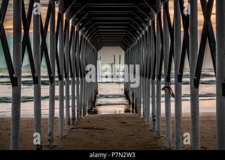 Perspective view from inside of a ferry terminal, a wooden-steel architecture on beach during sunset - Stock Photo