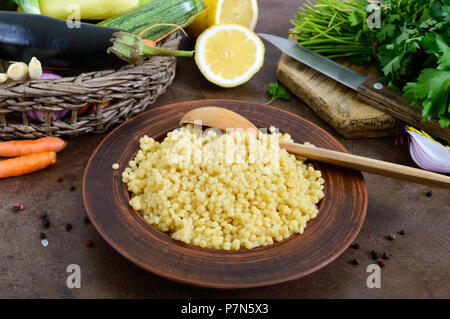 Delicious useful porridge cous cous in a clay plate and raw fresh vegetables in a basket, greens, lemon. Ingredients for cooking Tabbouleh. Vegetarian - Stock Photo