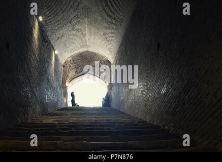 Iranian Muslim woman stands at light at the end of a tunnel and stairs at the entrance to a Silk Road underground water reservoir in Qazvin, Iran - Stock Photo