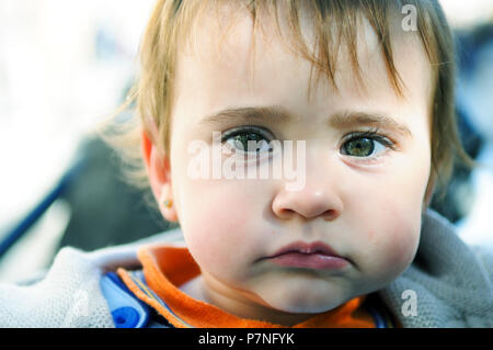 Close-up portrait of happy baby girl nine months old outdoors - Stock Photo