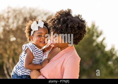 African American mother holding her daughter. - Stock Photo
