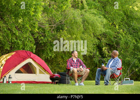 Friends talking and camping. - Stock Photo