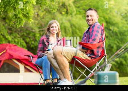 Couple talking and laughing on a camping trip. - Stock Photo