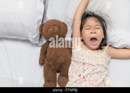 Little girl yawn and sleep on bed with teddy bear doll, Health care and relaxation concept - Stock Photo