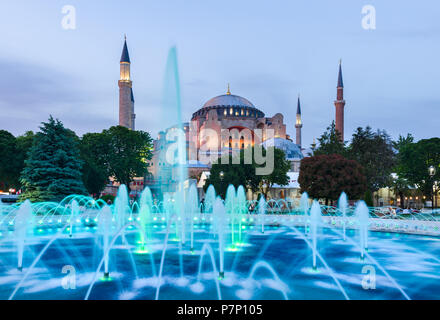 The Sultan Ahmad Maydan water fountain lit up with the Hagia Sophia museum in background at sunset, Istanbul, Turkey - Stock Photo