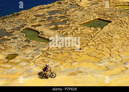 Mountain biking near Gozo salt pans, Xwejni Bay, Gozo Island, Malta - Stock Photo