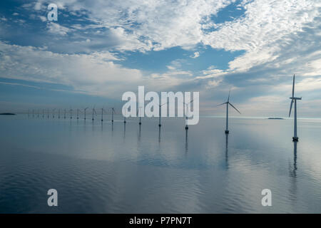 offshore windmill park alternative energy. windmills in the sea with reflection in the morning, denmark copenhagen - Stock Photo