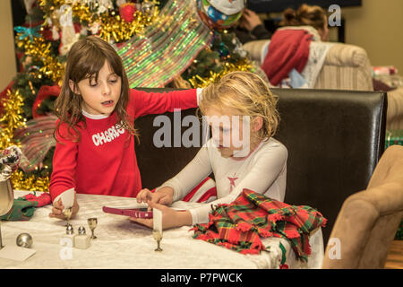 Petty, girl cousins playing with tablet at table, with Christmas tree in background. Cranbrook, BC, Canada. Modlel released- dark hair #104, blonde #1 - Stock Photo