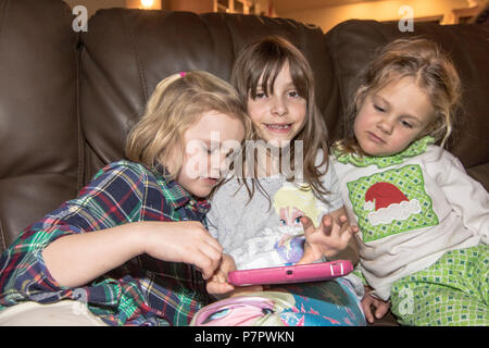 Three pretty, girl cousins,  playing with tablet, cuddled  on chair. Cranbrook, BC, Canada. Modlel released- left to right-#113, #104, #114 - Stock Photo