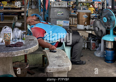 Thailand. A very hot day and a large man asleep in front of two cooling fans - Stock Photo
