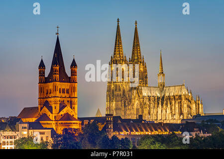The famous cathedral and Great St. Martin Church in Cologne at dusk - Stock Photo