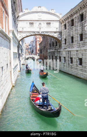 Gondolas passing under the Bridge of Sighs or Ponte dei Sospiri, San Marco, Venice, Veneto, Italy connecting the New Prison with the interrogation roo - Stock Photo
