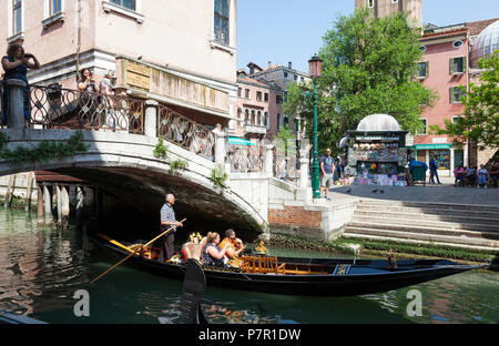Gondolier rowing tourists through Cannaregio, Venice, Veneto, italy in his sandolo, passing Campo Santi Apostoli under  a bridge - Stock Photo