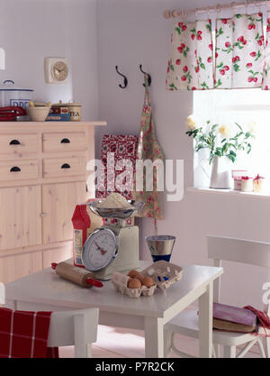 Chrome scales and a rolling pin with a box of fresh eggs on a small white table in a white economy style kitchen with cafe curtains - Stock Photo