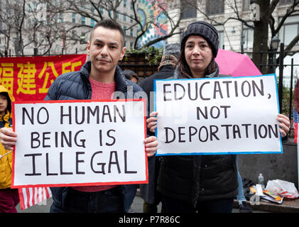 Two Hispanic Americans holding signs against deportation at a pro immigration ant-Trump Rally at Herald Square in Manhattan, New York City. - Stock Photo