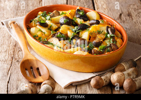 Fried wild mushrooms with potato slices, dill, parsley and cheddar cheese in a baking dish close-up on a table. horizontal - Stock Photo