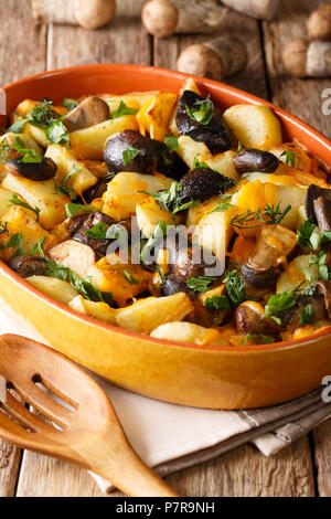 Baked potato wedges with forest mushrooms, cheddar cheese and herbs close-up in a baking dish on a table. vertical - Stock Photo