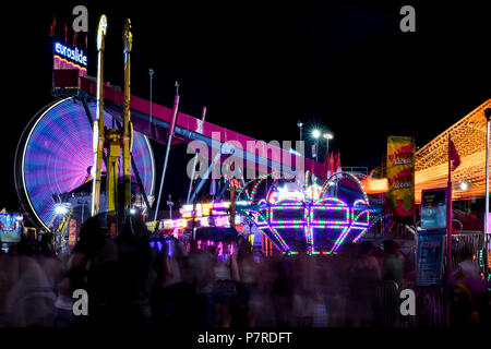Brightly coloured, motion-blurred Ferris wheel and other rides and ghostly people at the Calgary Stampede Midway located in Calgary, Alberta, Canada. - Stock Photo