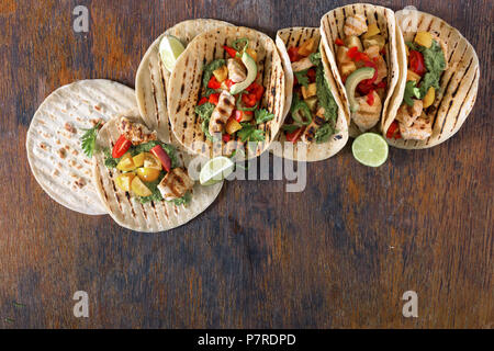 Healthy corn tortillas with grilled chicken fillet and guacamole sauce on wooden table, top view - Stock Photo