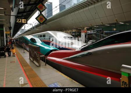 JAPAN - APR 2018 : Shinkansen series E5 HAYABUSA( green ) connect with series E6 KOMASHI( red ) at Sendai station, can see series 7 on background - Stock Photo