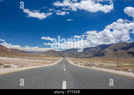 Emty road vanishing into HImalayas mountains in Ladakh, Northern India. Road trip concept - Stock Photo