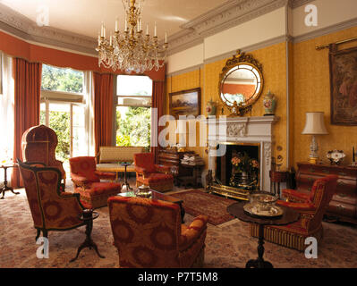 Red damask upholstered armchairs in yellow nineties drawing room - Stock Photo