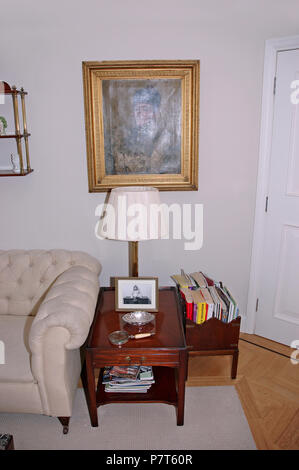 Gilt-framed picture above small table beside cream sofa in apartment living room - Stock Photo