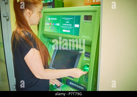 Syzran, Russia - June 20 , 2018: finance, money, bank and people concept - close up of hand taking receipt from atm machine of the Sberbank - Stock Photo
