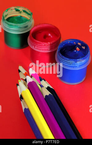 Set of pencils and containers with gouache on the table - Stock Photo
