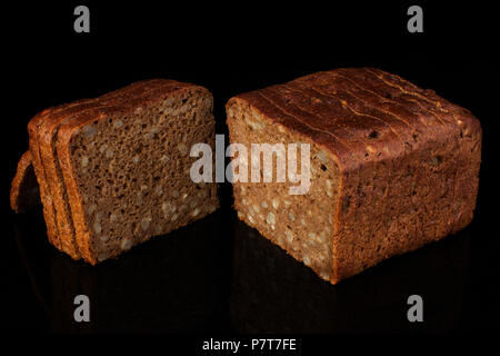 Ordinary bread with grains and sesame cut into pieces on a black background. Whole wheat bread - Stock Photo